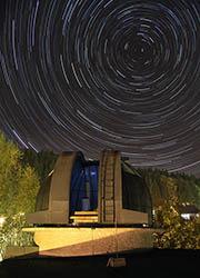 Časosběrný snímek kopule kysucké hvězdárny s otáčející se noční oblohou.